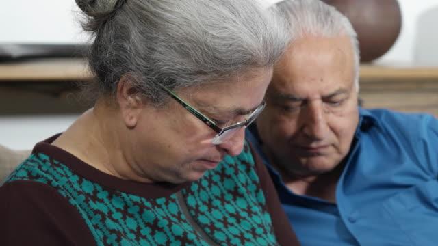 vídeos de stock e filmes b-roll de tracking, focus shift of an elder couple working on a wireless communication device - idoso na internet