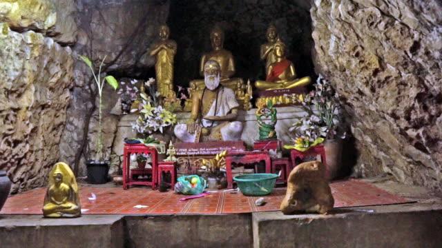 vídeos de stock, filmes e b-roll de acompanhamento em frente ao santuário de buddha caverna gruta, wat tham phousi, luang prabang, laos - grotto cave