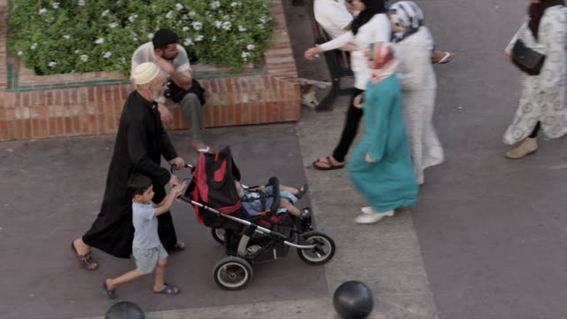 tracking from man pushing child in stroller to women walking - pushchair stock videos and b-roll footage