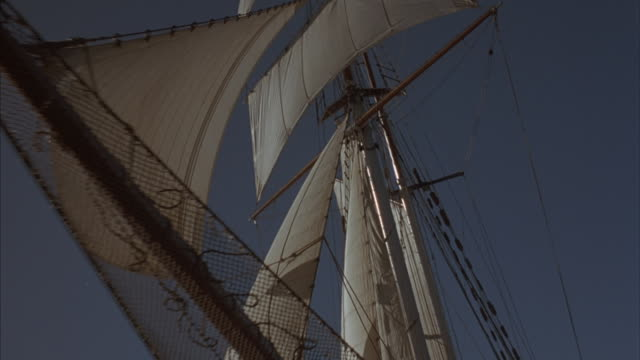 tracking in shot of the sun shining through the rigging of a sailing ship. - sailing boat stock videos and b-roll footage