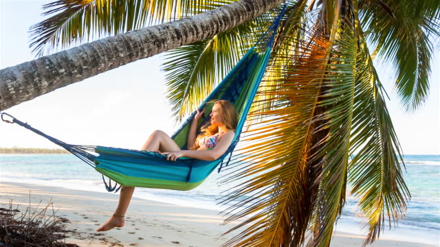 MS tracking in, young woman lying in hammock at tropical beach