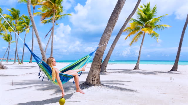 vídeos y material grabado en eventos de stock de ws tracking in, young woman lying in hammock at tropical beach - coco fruta tropical