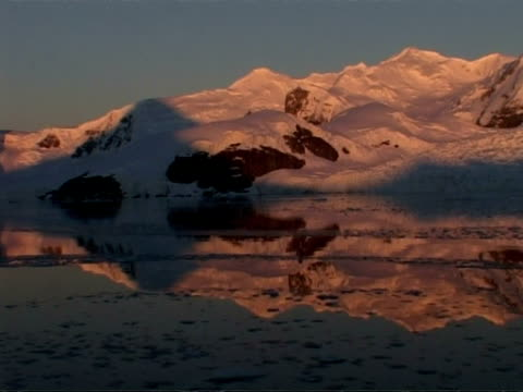 wa tracking left past ice floes and mountainous coastline at dusk, paradise bay area, antarctic peninsula - icecap stock videos & royalty-free footage