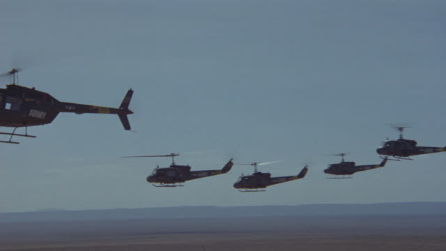 tracking left shot of a group of helicopters flying in formation. - formationsfliegen stock-videos und b-roll-filmmaterial