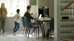 Tracking left shot of middle aged man using laptop computer sitting at table in domestic kitchen. Little daughter running downstairs to him, caring mother giving her glass of orange juice and kissing