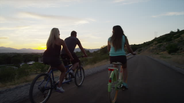 Tracking medium shot of family bike riding on road at sunset / Cedar Hills, Utah, United States