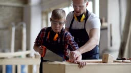 Tracking medium shot of middle aged carpenter teaching son how to cut wooden plank with hand saw standing at workbench in carpentry shop, both wearing aprons and protective eyewear