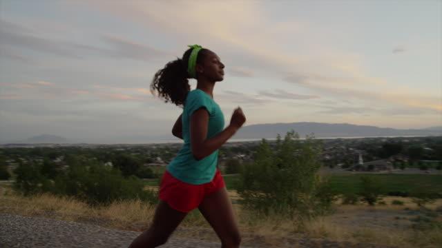 tracking medium shot of teenage girl running on road / cedar hills, utah, united states - adolescence stock videos & royalty-free footage