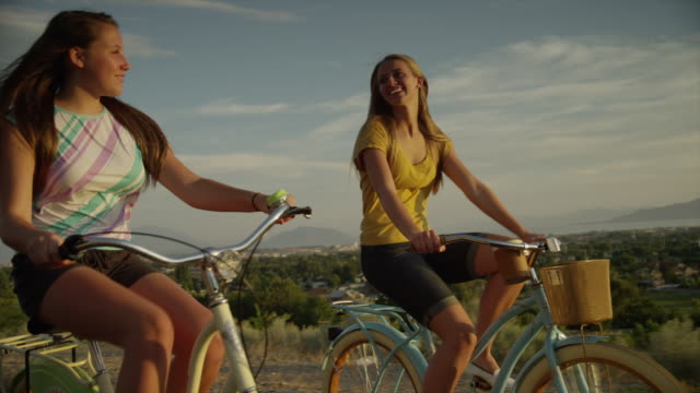 Tracking medium shot of young women bike riding on road / Cedar Hills, Utah, United States
