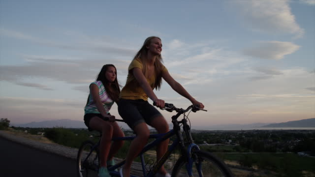 Tracking medium shot of young women riding tandem bicycle on road / Cedar Hills, Utah, United States