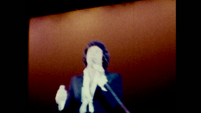 tracking medium view of tom jones singing on stage with microphone at the long beach amphitheater - typisch walisisch stock-videos und b-roll-filmmaterial
