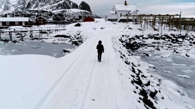 tracking of man walking on snow road in fishing village and frosty in gloomy weather - pulse trace stock videos & royalty-free footage