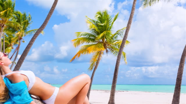 ms tracking out, young woman lying on palm tree at tropical beach - tropical tree stock videos & royalty-free footage