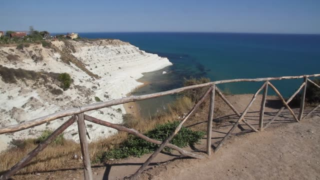 tracking past a fence to reveal the spectacular white cliffs of the stair of the turks, sicily - rock strata stock videos & royalty-free footage