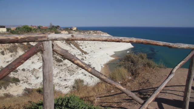 vidéos et rushes de tracking past a fence to reveal the spectacular white cliffs of the stair of the turks, sicily - strate géologique