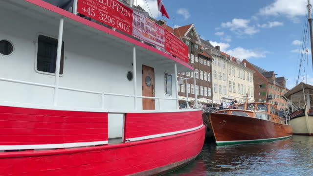 tracking past colourful boats moored in nyhavn harbour from a tour boat, copenhagen - regione dell'oresund video stock e b–roll