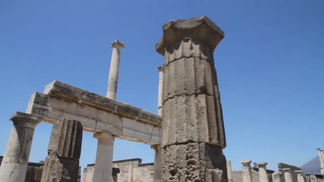 tracking past columns of the basilica towards the ruined colonnades of the forum, pompeii, napoli - unesco world heritage site stock videos & royalty-free footage