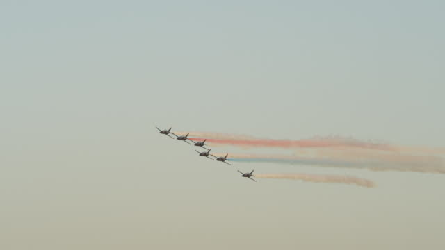 tracking patriots jet team flying in formation and releasing colored smoke - formationsfliegen stock-videos und b-roll-filmmaterial