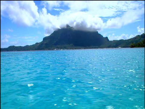 vidéos et rushes de tracking right of coastline across blue water with mountains in background tourists snorkelling in clear blue water near beach french polynesia - dom tom