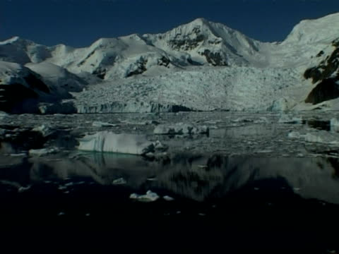 wa tracking right past mountainous horizon reflected in still sea with ice floes, paradise bay area, antarctic peninsula - antarctic peninsula stock videos & royalty-free footage