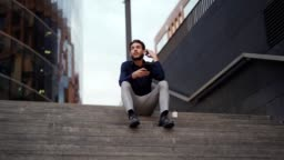Tracking right slow motion shot of young businessman adjusting hair sitting on steps of modern office building with cell phone in his hands and contemplating