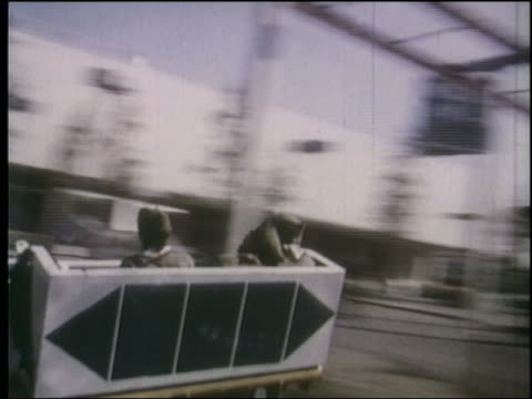 1964 tracking shot 3 boy scouts on rotating amusement park ride at ny world's fair - 1964年点の映像素材/bロール