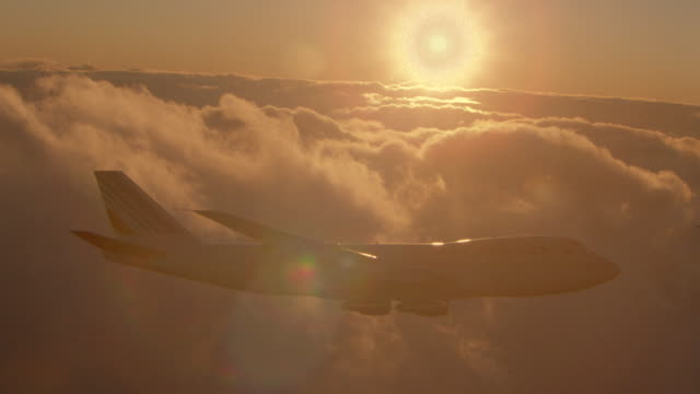 aerial backlit tracking shot 747 jet flying next to orange clouds, tilting + turning away from camera at sunset - flying stock videos & royalty-free footage