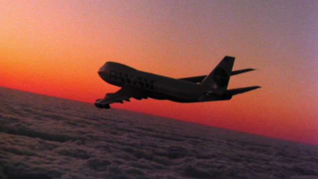 aerial tracking shot 747 jet flying over sea of clouds at sunrise/set - air to air shot stock videos and b-roll footage