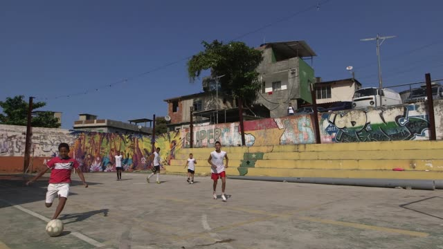 Tracking Shot a group of children and teenagers play football in Vidigal favela Rio de Janeiro Brazil on June 7 2013