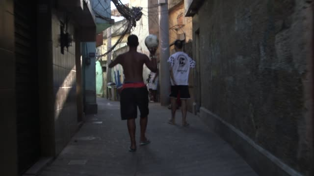 Tracking Shot a teenager is is walking through the narrow streets of Morro da Sao Carlos favela with a football in his hand on June 5 2013
