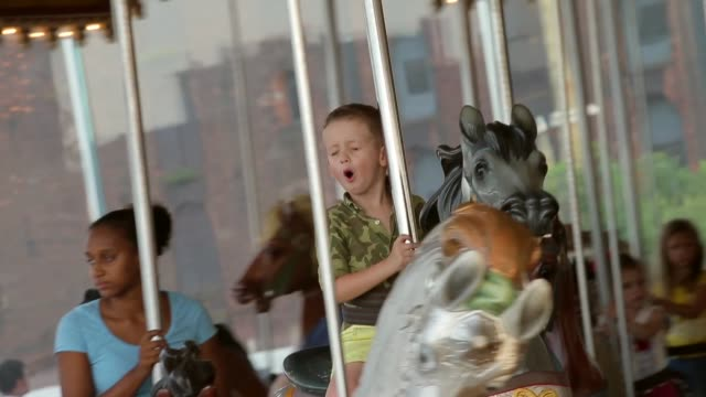 Tracking Shot A Young Boy Riding the Carousel Janes Carousel is a classic 3row machine with 48 exquisitely carved horses and two superb chariots It...