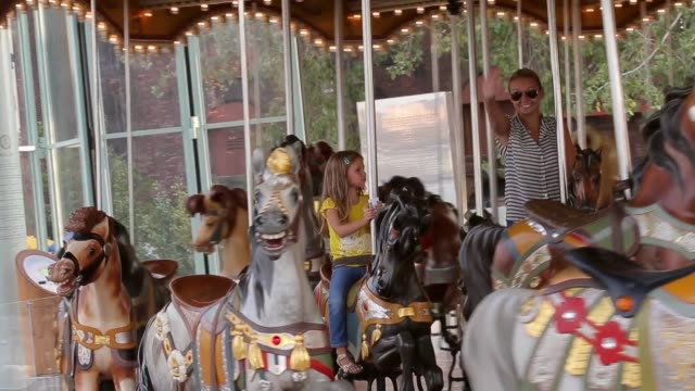 Tracking Shot a young girl and her mother are waving to the camera as they go past in the carousel Janes Carousel is a classic 3row machine with 48...