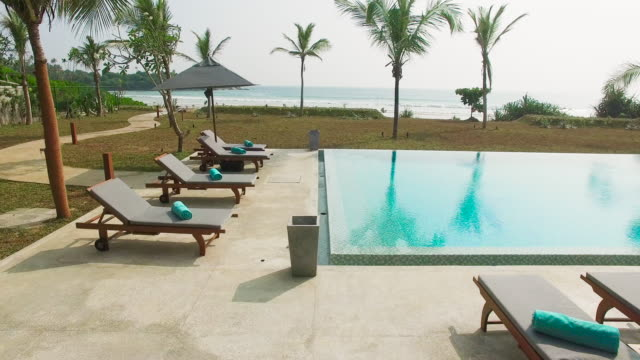Kamerafahrt über dem Swimmingpool des Hotels in Richtung Sandstrand und Meer