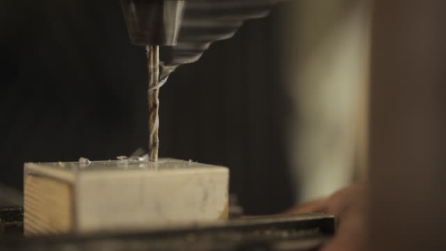 tracking shot across a drill drilling into a small block of wood and metal. - drill bit stock videos and b-roll footage