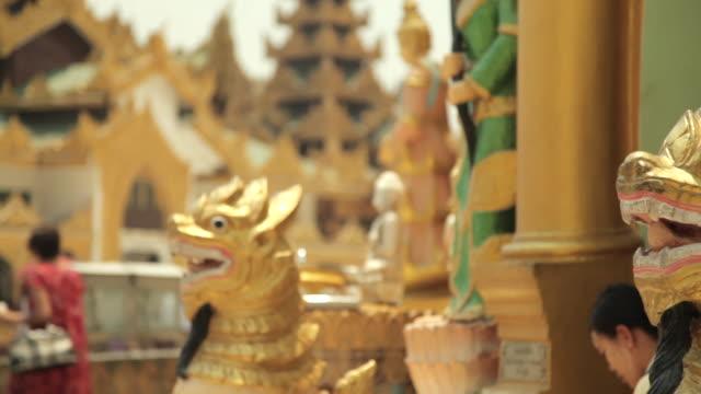 Tracking shot across beautifully gilded creatures at the Shwedagon Pagoda.