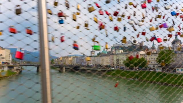 tracking shot, across bridge adorned with padlocks symbolising love - 幸運点の映像素材/bロール