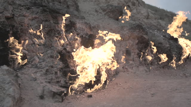 tracking shot across flames erupting from fissures in the ground at an oil field near baku. - baku video stock e b–roll