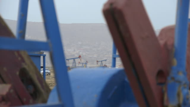 tracking shot across operational pumpjacks at an oil field near baku. - baku video stock e b–roll