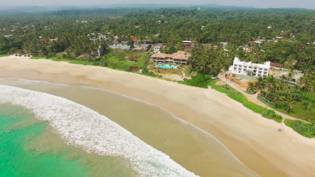 Tracking shot across sea and beach towards luxury tourist resort