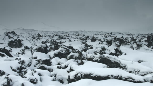 Tracking shot across snow covered rocks at the Snaefellsnes peninsula.