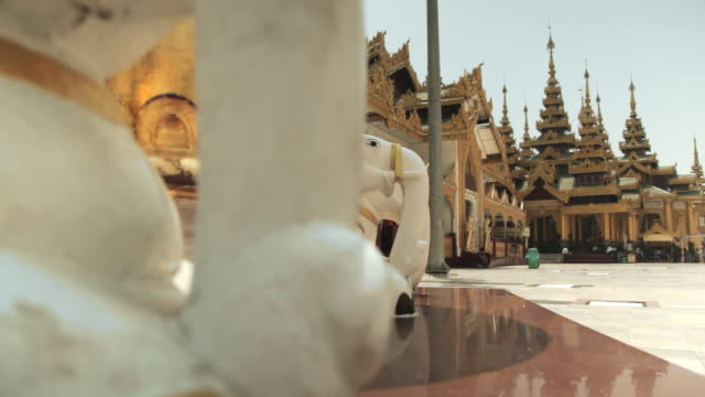 Tracking shot across stone elephants situated in the Shwedagon Pagoda complex.
