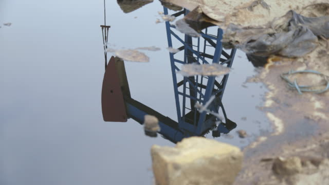 tracking shot across the reflection of an operational pumpjack in a puddle of water. - baku video stock e b–roll
