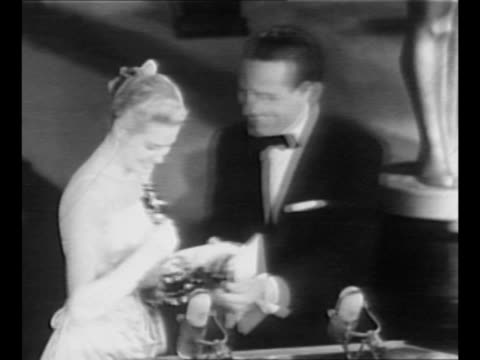 Tracking shot actress Grace Kelly walks onstage at the 27th Academy Awards and accepts Oscar from William Holden who kisses her cheek / WS audience /...
