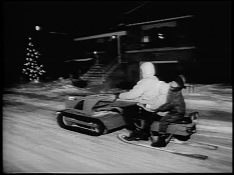b/w 1964 tracking shot adult + two children riding primitive snowmobile in street at night / newsreel - ウィンタースポーツ点の映像素材/bロール