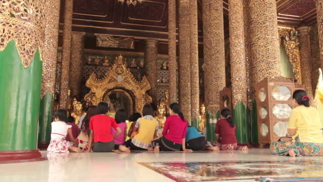 tracking shot along a group of people sitting in front of a buddhist shrine at the shewdagon pagoda, yangon. - girls videos stock videos & royalty-free footage