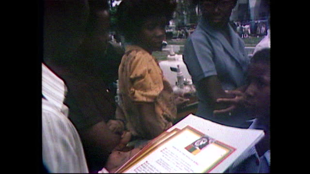 tracking shot along a queue of people, crowded together, waiting outside bob marley's state funeral; 1981. - ボブ・マーリー点の映像素材/bロール