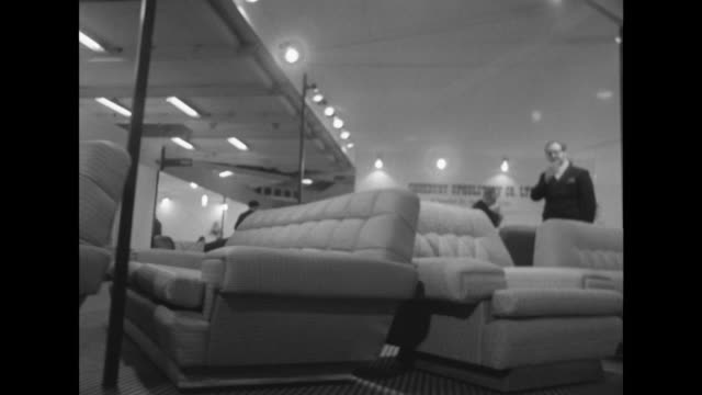 tracking shot along a row of chairs and sofas at a furniture exhibition - chair stock videos & royalty-free footage