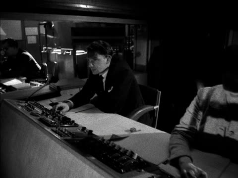 vidéos et rushes de tracking shot along a television studio control desk. 1958. - bbc