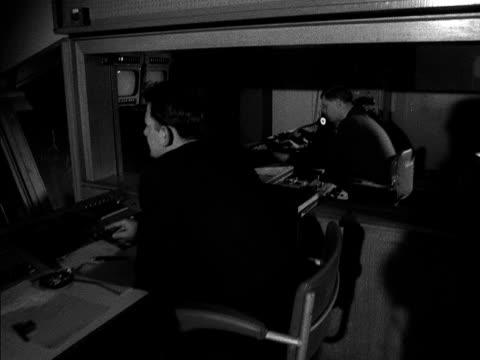 vídeos y material grabado en eventos de stock de tracking shot along a television studio control desk 1958 - bbc