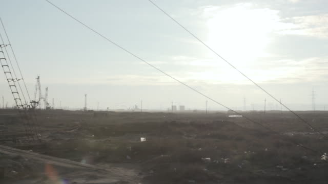 tracking shot along an oil field near the city of baku. - baku video stock e b–roll